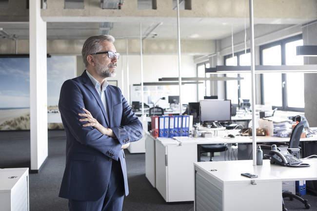 Empresario de pie en la oficina con los brazos cruzados y pensar - foto de stock