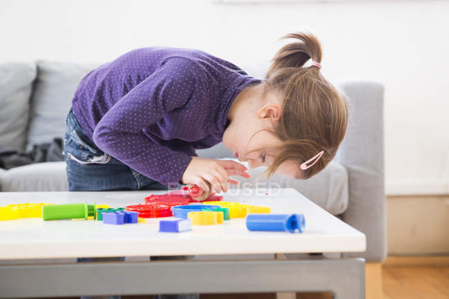 Little girl rolling out modeling clay at desk — Stock Photo