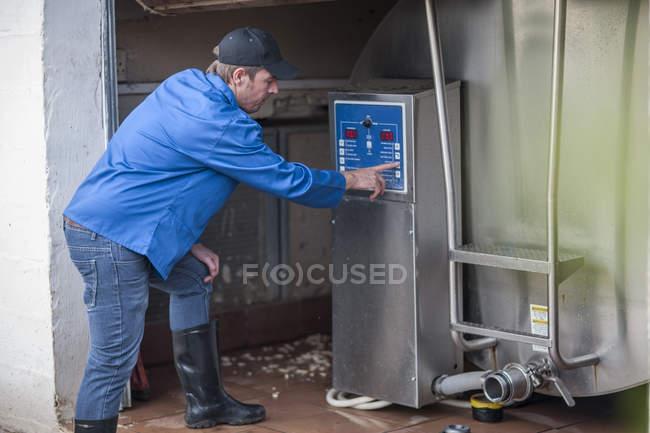 Farmer adjusting dairy farm machinery — Stock Photo
