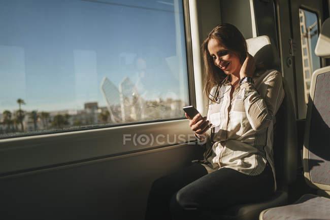 Donna sorridente su un treno che guarda il cellulare — Foto stock