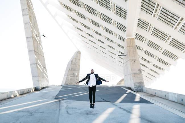 Uomo d'affari saltando sotto pannelli solari — Foto stock