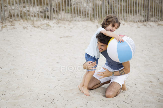 Father and son on the beach playing with a colorful ball — Stock Photo
