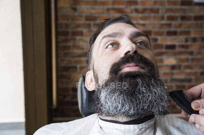 Barber cutting man beard — Stock Photo