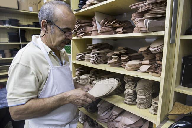 Sapateiro selecionando solas de sapato de uma prateleira em sua oficina — Fotografia de Stock
