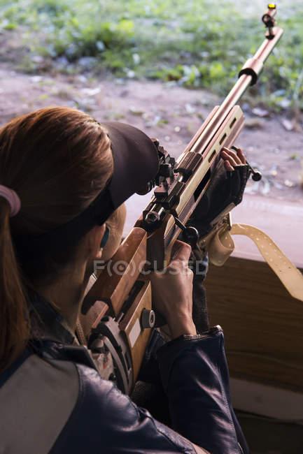 Mulher com um rifle esportivo com o objetivo em um campo de tiro — Fotografia de Stock