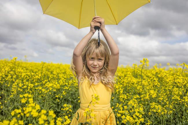 Portrait de petite fille blonde avec parapluie jaune portant une robe jaune debout dans un champ de viol — Photo de stock