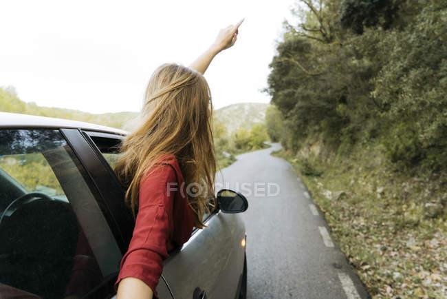Heureuse jeune femme penchée par la fenêtre de la voiture — Photo de stock