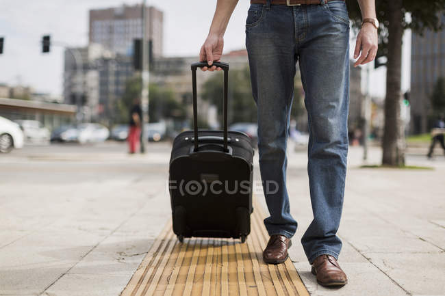 Legs of businessman with suitcase on pavement — Stock Photo