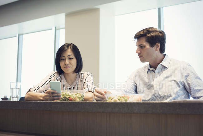 Colleagues in office having lunch together, woman looking at smart phone — Stock Photo