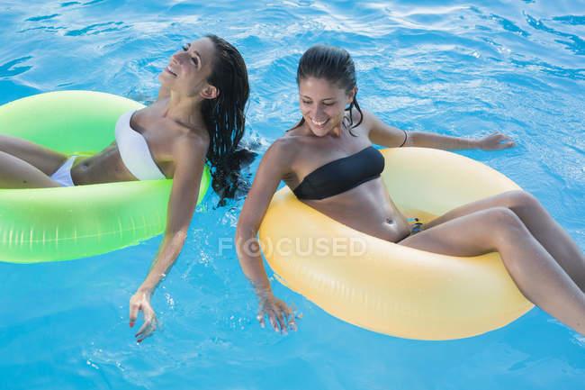 Дві молоді жінки плаваючий на воді в басейні — стокове фото