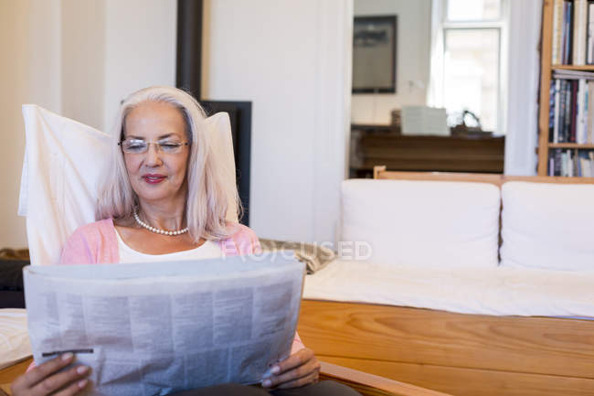 Reife Frau im Sessel zu Hause lesen Zeitung — Stockfoto