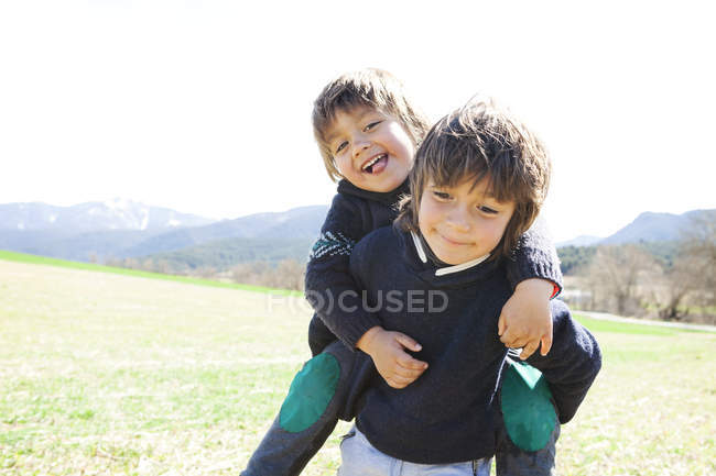 Portrait of little boy carrying his brother piggyback — Stock Photo