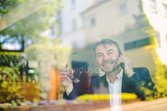 Empresário usando telefone celular no café — Fotografia de Stock
