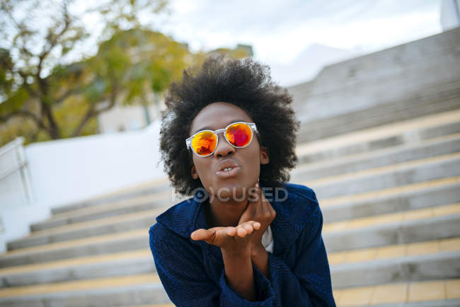 Portrait of young woman wearing mirrored sunglasses throwing a kiss to camera — Stock Photo