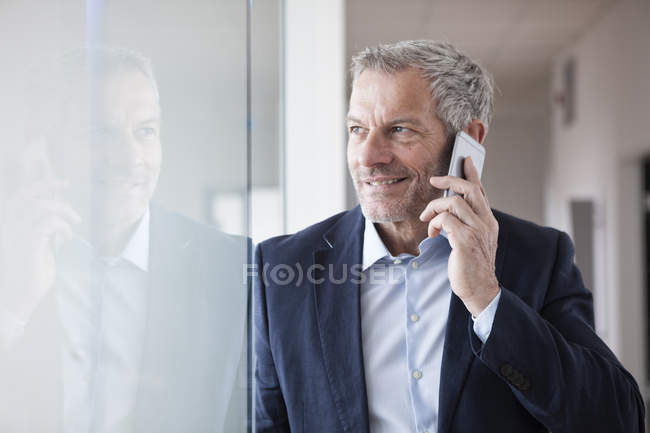 Successful businessman standing in his office and talking on the smartphone — Stock Photo