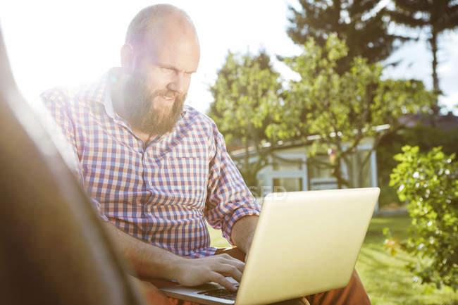 Jovem trabalhando com laptop no jardim — Fotografia de Stock