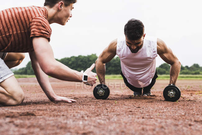 Athlete doing pushups with dumbbells on sports field supported by his training partner — Stock Photo