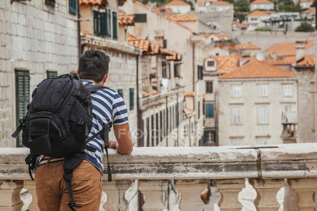 Vista posteriore del turista con lo zaino guardando la città — Foto stock