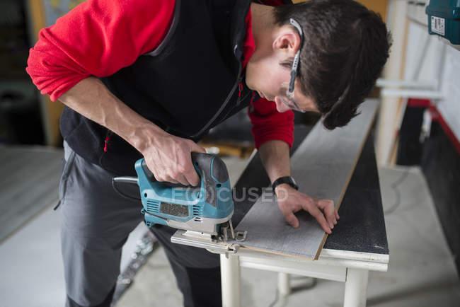 Людина вирізки шматків ламінований підлогу з головоломки — стокове фото