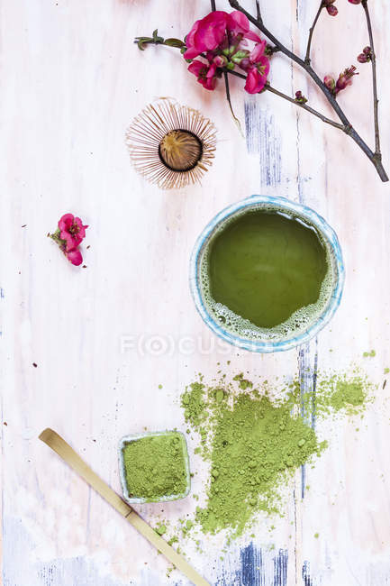 Matcha tea in bowl, with powder, spoon, chasen and pink flowers — Stock Photo