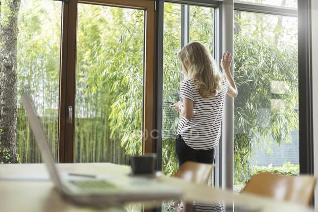Donna con cellulare in piedi alla finestra — Foto stock