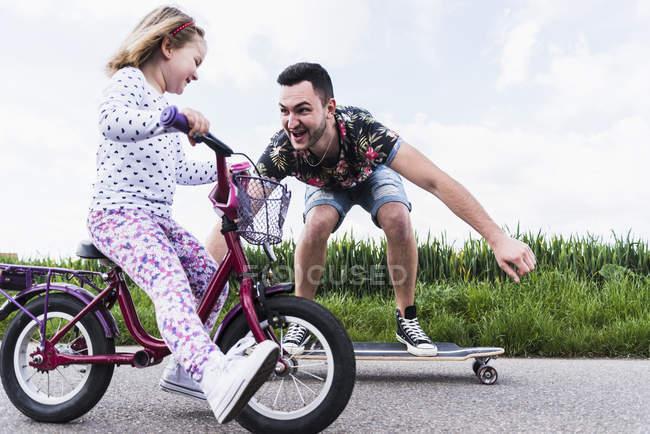 Батько на скейтборді супроводжуючих дочка на велосипеді — стокове фото