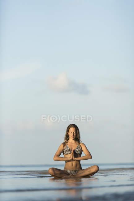 Thailand, woman meditating on beach — Stock Photo