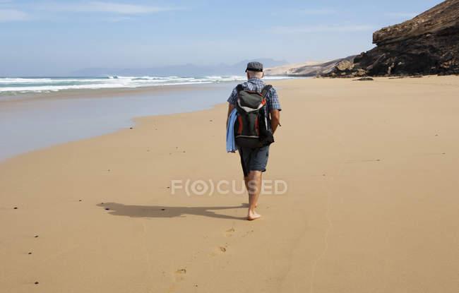 Испания, Канарские острова, Фуэртевентура, пляж Barlovento. Сзади портрет человека на прогулку — стоковое фото