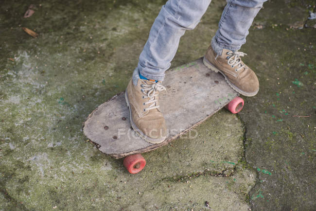 Legs of boy on an old skateboard — Stock Photo