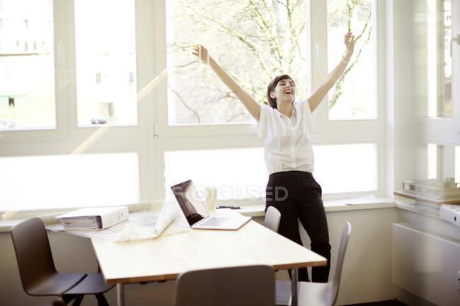 Смеющаяся женщина делает упражнения на растяжку в своем офисе — стоковое фото