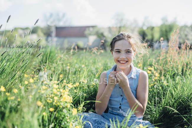 Ragazza seduta nel prato fiorito — Foto stock