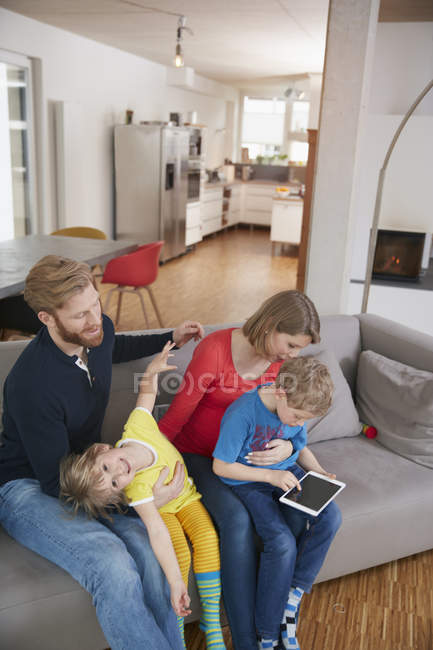 Family of four with digital tablet on couch — Stock Photo