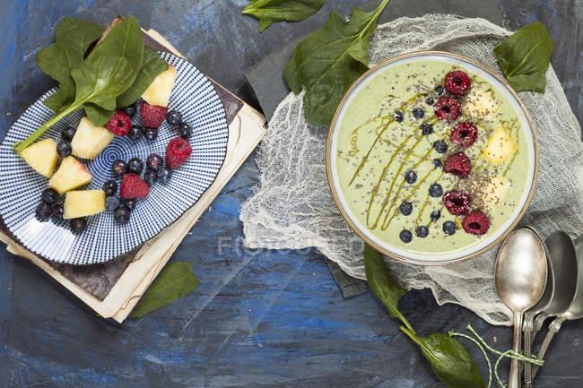 Draufsicht auf garnierte grüne Smoothie-Schüssel mit Beeren und in Scheiben geschnittenen Bananen — Stockfoto