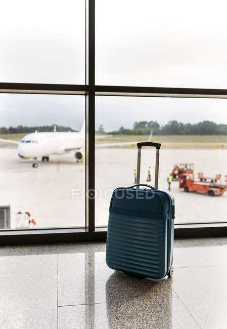 Чемодан в аэропорту, пассажирский самолет и багажный вагон на заднем плане — стоковое фото