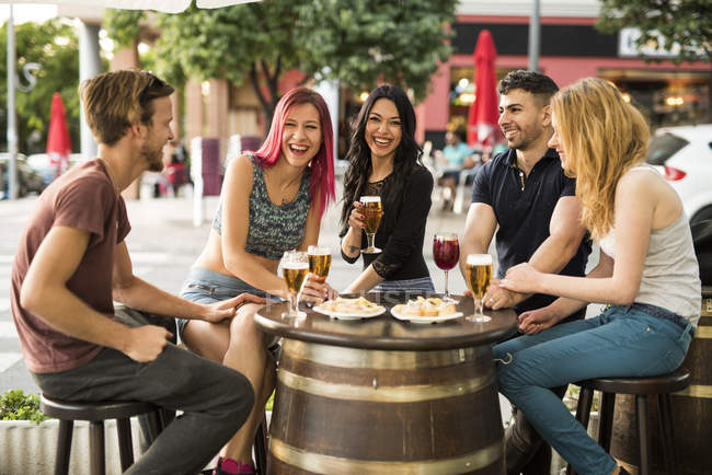 Laughing friends having fun in outdoor bar — Stock Photo