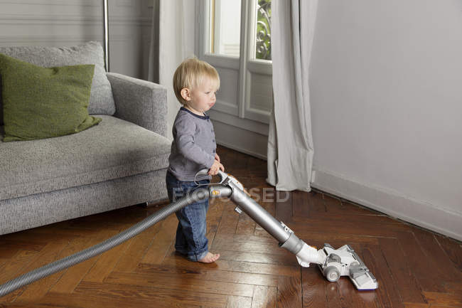 Toddler Vacuuming A Wooden Floor In The Living Room Stock Photo