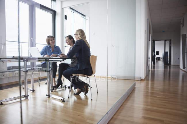 Three businesswomen having meeting in modern office — Stock Photo