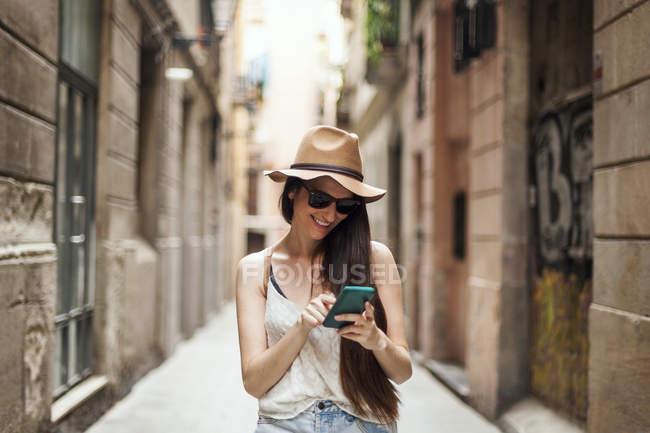 Молодой турист, путешествующий по улицам Барселоны с помощью мобильного телефона — стоковое фото