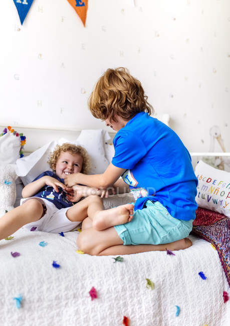 Boy tickling his little brother on the couch — Stock Photo