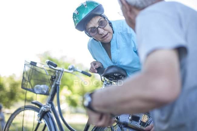 Mulher idosa de bicicleta conversando com o homem — Fotografia de Stock