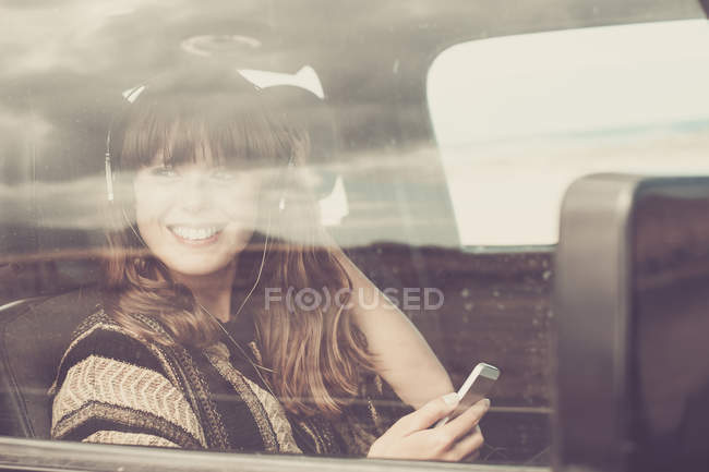 Young woman travelling in car listening music — Stock Photo