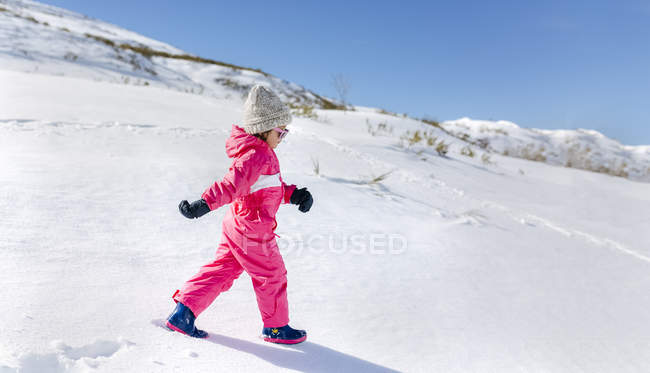 Cute little girl in winter outfit walking in snow — Stock Photo