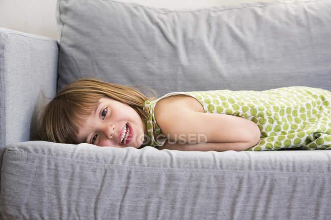 Retrato de una chica sonriente acostada en el sofá - foto de stock