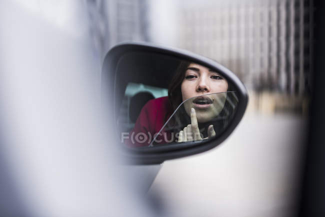 Jolie femme assise en voiture appliquant le maquillage dans le miroir d'aile — Photo de stock
