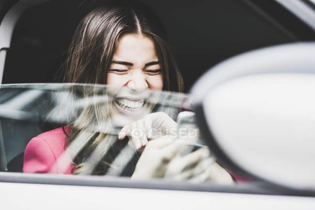 Bruna donna seduta in auto ridendo sui messaggi di testo — Foto stock