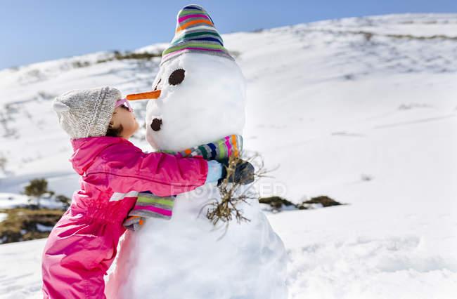 Ragazza felice che gioca con pupazzi di neve in inverno — Foto stock