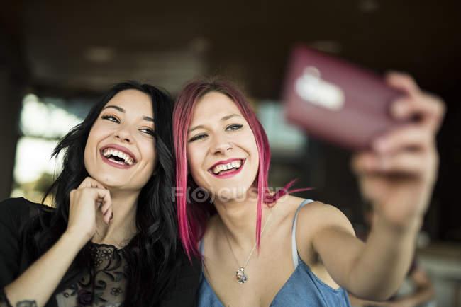Junge Frauen sitzen im Café und nehmen selfie — Stockfoto