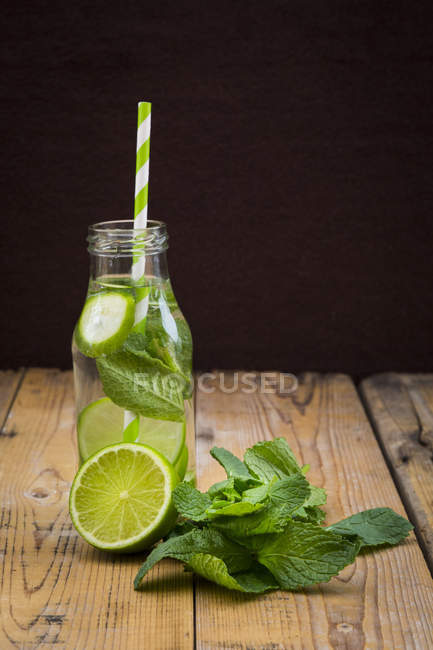 Glass bottle of water flavored with lime and mint — Stock Photo