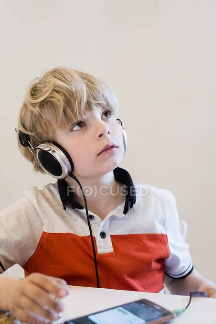 Мальчик носить наушники, глядя на стол — стоковое фото