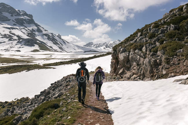 Spain, Asturias, Somiedo, couple hiking in snowy mountains — Stock Photo